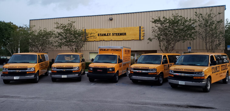 Fleet of air duct and carpet cleaning service trucks parked at the Stanley Steemer office in Port Saint Lucie, Florida.