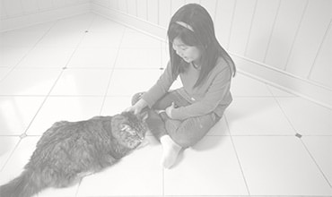 Young girl sitting on a tile floor with her cat.